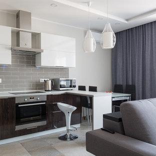 Выдающиеся фото от архитекторов и дизайнеров интерьера: угловая кухня-гостиная в современном стиле с плоскими фасадами, темными деревянными фасадами, серым фартуком, техникой из нержавеющей стали, серым полом и белой столешницей без острова