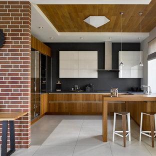 На фото: большая отдельная, п-образная кухня в современном стиле с монолитной раковиной, плоскими фасадами, фасадами цвета дерева среднего тона, черным фартуком, полуостровом, серым полом и черной столешницей