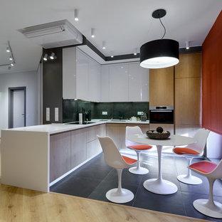 Пример оригинального дизайна: угловая кухня-гостиная в современном стиле с плоскими фасадами, техникой из нержавеющей стали и черным полом без острова
