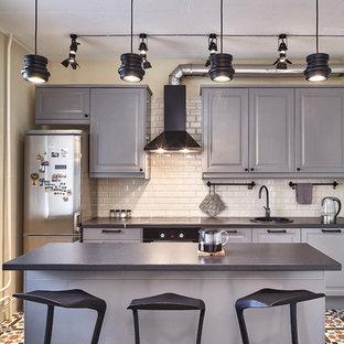 Идея дизайна: прямая кухня в современном стиле с накладной раковиной, фасадами с выступающей филенкой, серыми фасадами, белым фартуком, фартуком из плитки кабанчик, черной техникой, островом и разноцветным полом