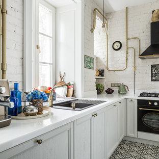 Стильный дизайн: маленькая угловая кухня в стиле лофт с столешницей из акрилового камня, полом из керамической плитки, накладной раковиной, фасадами с утопленной филенкой, белыми фасадами, белым фартуком, фартуком из кирпича, черной техникой, черным полом, обеденным столом и белой столешницей без острова - последний тренд