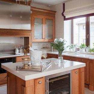 Пример оригинального дизайна интерьера: угловая кухня в классическом стиле с монолитной раковиной, фасадами цвета дерева среднего тона, белым фартуком, техникой из нержавеющей стали, островом, бежевым полом, белой столешницей и фасадами с утопленной филенкой