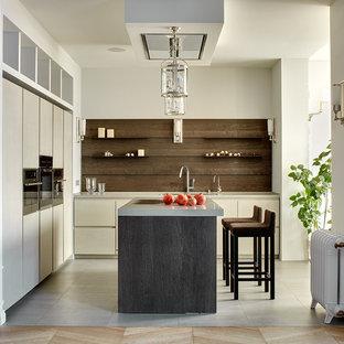 Свежая идея для дизайна: угловая кухня-гостиная в современном стиле с плоскими фасадами, островом, бежевым фартуком, полом из керамогранита и серыми фасадами - отличное фото интерьера