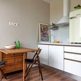 Пример оригинального дизайна интерьера: маленькая линейная кухня в современном стиле с обеденным столом, накладной раковиной, плоскими фасадами, белыми фасадами, белым фартуком, фартуком из стекла, цветной техникой, темным паркетным полом, коричневым полом и белой столешницей