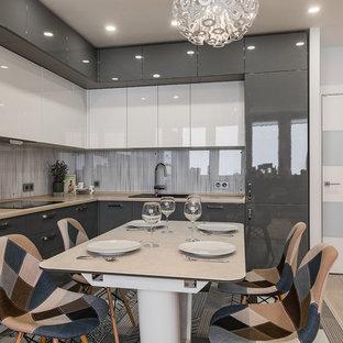 Идея дизайна: угловая кухня в современном стиле с обеденным столом, накладной раковиной, плоскими фасадами, серыми фасадами, белым фартуком, фартуком из стекла, техникой из нержавеющей стали, светлым паркетным полом и бежевой столешницей без острова