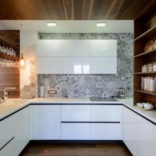 Пример оригинального дизайна: п-образная кухня-гостиная в современном стиле с монолитной раковиной, плоскими фасадами, белыми фасадами, серым фартуком, паркетным полом среднего тона и коричневым полом без острова