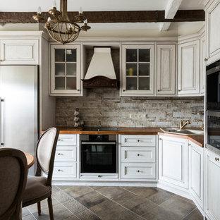 На фото: угловая кухня в классическом стиле с накладной раковиной, фасадами с выступающей филенкой, белыми фасадами, бежевым фартуком и черной техникой с