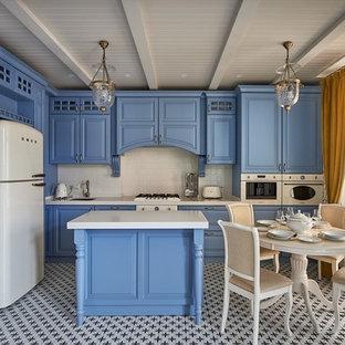 Стильный дизайн: угловая кухня в классическом стиле с обеденным столом, врезной раковиной, фасадами с выступающей филенкой, синими фасадами, белым фартуком, белой техникой, островом, разноцветным полом и белой столешницей - последний тренд