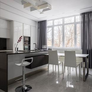 Стильный дизайн: параллельная кухня в современном стиле с плоскими фасадами, белыми фасадами, черной техникой, островом, черной столешницей, обеденным столом, черным фартуком и белым полом - последний тренд