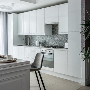 На фото: кухни в современном стиле с накладной раковиной, плоскими фасадами, белыми фасадами, серым фартуком, фартуком из плитки мозаики, техникой из нержавеющей стали, бежевым полом и белой столешницей