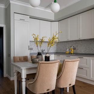 Идея дизайна: угловая кухня в стиле современная классика с фасадами с утопленной филенкой, белыми фасадами, серым фартуком, фартуком из плитки мозаики, паркетным полом среднего тона, коричневым полом, серой столешницей и обеденным столом без острова