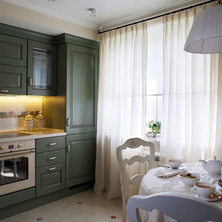 Small shabby-chic style l-shaped separate kitchen in Moscow with beige floor, an undermount sink, recessed-panel cabinets, green cabinets, solid surface benchtops, white splashback, ceramic splashback, white appliances, porcelain floors and white benchtop.