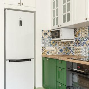 На фото: линейные кухни в скандинавском стиле с обеденным столом, фартуком из керамической плитки, фасадами с утопленной филенкой, зелеными фасадами, деревянной столешницей, разноцветным фартуком, черной техникой и коричневой столешницей