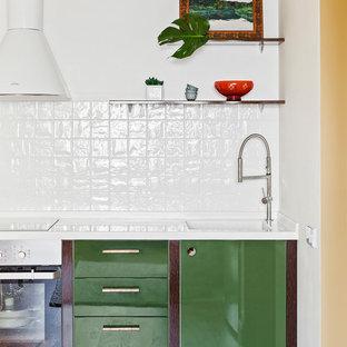 Пример оригинального дизайна: маленькая прямая кухня-гостиная в стиле современная классика с монолитной раковиной, плоскими фасадами, зелеными фасадами, столешницей из акрилового камня, белым фартуком, фартуком из керамической плитки, паркетным полом среднего тона, коричневым полом, белой столешницей и техникой из нержавеющей стали без острова