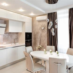 На фото: линейная кухня в современном стиле с обеденным столом, монолитной раковиной, плоскими фасадами, белыми фасадами, бежевым фартуком, фартуком из каменной плитки и черной техникой без острова с