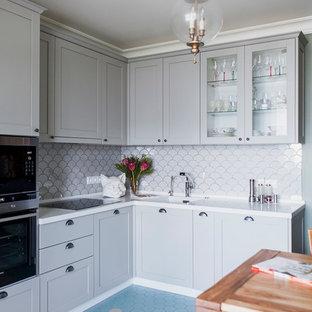 Новый формат декора квартиры: угловая кухня в стиле современная классика с серыми фасадами, белым фартуком, техникой из нержавеющей стали, разноцветным полом, обеденным столом, одинарной раковиной и стеклянными фасадами без острова