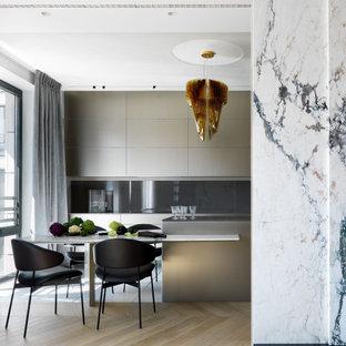 На фото: параллельная кухня-гостиная среднего размера в современном стиле с плоскими фасадами, серыми фасадами, серым фартуком, фартуком из стекла, техникой под мебельный фасад, светлым паркетным полом, полуостровом, бежевым полом, серой столешницей и барной стойкой
