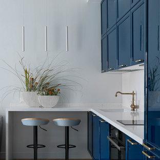 Неиссякаемый источник вдохновения для домашнего уюта: кухня в современном стиле с врезной раковиной, фасадами с утопленной филенкой, синими фасадами, черной техникой, светлым паркетным полом, полуостровом и белой столешницей