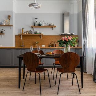 サンクトペテルブルクの中くらいの北欧スタイルのおしゃれなキッチン (ドロップインシンク、レイズドパネル扉のキャビネット、グレーのキャビネット、木材カウンター、茶色いキッチンパネル、木材のキッチンパネル、黒い調理設備、ラミネートの床、アイランドなし、茶色い床、茶色いキッチンカウンター) の写真