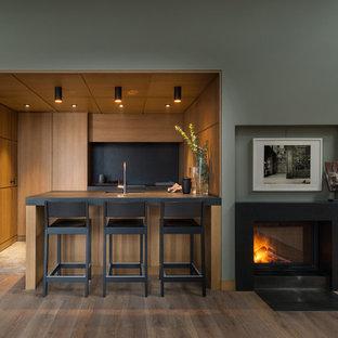 На фото: маленькая параллельная кухня-гостиная в современном стиле с врезной раковиной, плоскими фасадами, фасадами цвета дерева среднего тона, гранитной столешницей, черным фартуком, островом и черной столешницей