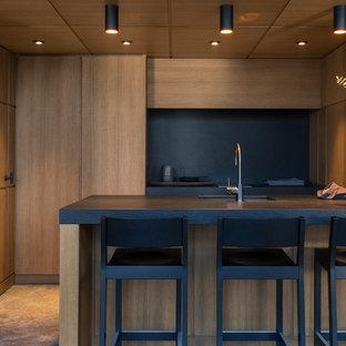 Пример оригинального дизайна: маленькая параллельная кухня-гостиная в современном стиле с врезной раковиной, плоскими фасадами, фасадами цвета дерева среднего тона, столешницей из гранита, черным фартуком, островом и черной столешницей