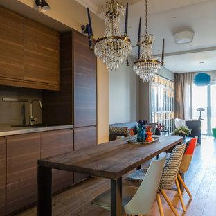 Неиссякаемый источник вдохновения для домашнего уюта: линейная кухня-гостиная в современном стиле с накладной раковиной, плоскими фасадами, темными деревянными фасадами, столешницей из нержавеющей стали, техникой под мебельный фасад, паркетным полом среднего тона, коричневым полом и серой столешницей без острова