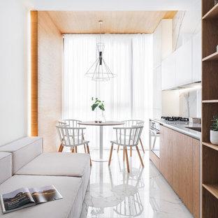 На фото: маленькая линейная кухня - столовая в современном стиле с врезной раковиной, плоскими фасадами, фасадами цвета дерева среднего тона, белым фартуком, белым полом и белой столешницей без острова с