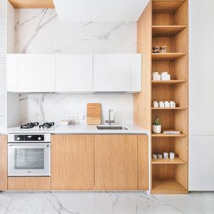 Свежая идея для дизайна: линейная кухня в современном стиле с врезной раковиной, плоскими фасадами, фасадами цвета дерева среднего тона, белым фартуком, фартуком из каменной плиты, белой техникой, белым полом и белой столешницей - отличное фото интерьера