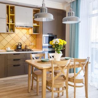Источник вдохновения для домашнего уюта: угловая кухня-гостиная в современном стиле с фасадами с утопленной филенкой, коричневыми фасадами, желтым фартуком, техникой из нержавеющей стали, бежевым полом и белой столешницей