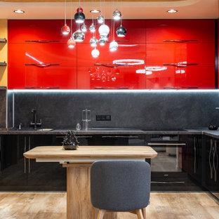Идея дизайна: угловая кухня в современном стиле с накладной раковиной, плоскими фасадами, красными фасадами, черным фартуком, черной техникой, островом, бежевым полом и черной столешницей