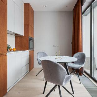 Пример оригинального дизайна: маленькая прямая кухня в современном стиле с обеденным столом, врезной раковиной, плоскими фасадами, серыми фасадами, техникой под мебельный фасад, светлым паркетным полом, бежевым полом и серой столешницей без острова