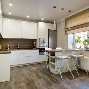 Photo of a large contemporary l-shaped open plan kitchen in Novosibirsk with a drop-in sink, flat-panel cabinets, white cabinets, wood benchtops, brown splashback, timber splashback, stainless steel appliances, vinyl floors, with island, brown floor and brown benchtop.
