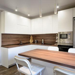 ノボシビルスクの広いコンテンポラリースタイルのおしゃれなキッチン (ドロップインシンク、フラットパネル扉のキャビネット、白いキャビネット、木材カウンター、茶色いキッチンパネル、木材のキッチンパネル、シルバーの調理設備、クッションフロア、茶色い床、茶色いキッチンカウンター) の写真
