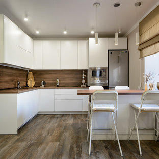 Design ideas for a large contemporary l-shaped kitchen in Novosibirsk with a drop-in sink, flat-panel cabinets, white cabinets, wood benchtops, brown splashback, timber splashback, stainless steel appliances, vinyl floors, brown floor, brown benchtop and a peninsula.
