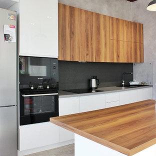 ノボシビルスクの広いコンテンポラリースタイルのおしゃれなキッチン (アンダーカウンターシンク、フラットパネル扉のキャビネット、白いキャビネット、木材カウンター、黒いキッチンパネル、モザイクタイルのキッチンパネル、黒い調理設備、クッションフロア、ベージュの床、茶色いキッチンカウンター) の写真