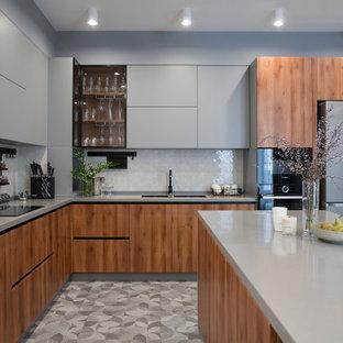 Пример оригинального дизайна: большая отдельная, угловая кухня в современном стиле с двойной раковиной, плоскими фасадами, серыми фасадами, столешницей из акрилового камня, белым фартуком, фартуком из плитки мозаики, черной техникой, полом из керамогранита, островом, серым полом и серой столешницей