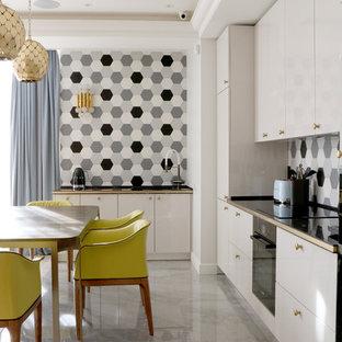 На фото: угловая кухня в современном стиле с плоскими фасадами, белыми фасадами, разноцветным фартуком, черной техникой, серым полом и черной столешницей без острова с