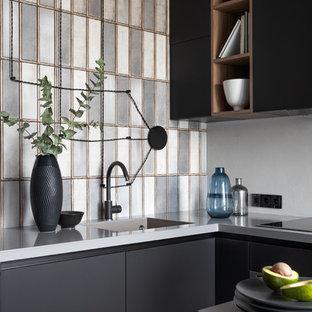 Свежая идея для дизайна: маленькая п-образная кухня в стиле лофт с плоскими фасадами, черными фасадами, одинарной раковиной, разноцветным фартуком и серой столешницей - отличное фото интерьера