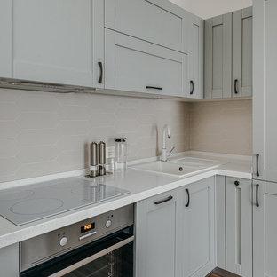 Создайте стильный интерьер: угловая кухня в скандинавском стиле с накладной раковиной, фасадами в стиле шейкер, серыми фасадами, бежевым фартуком, техникой из нержавеющей стали, коричневым полом и белой столешницей без острова - последний тренд