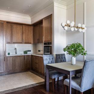 Свежая идея для дизайна: кухня в стиле современная классика с обеденным столом, фасадами цвета дерева среднего тона, белым фартуком и белой столешницей - отличное фото интерьера