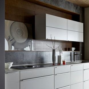На фото: кухня в современном стиле с плоскими фасадами, серым фартуком, белым полом, серой столешницей, одинарной раковиной и серыми фасадами с