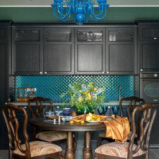 На фото: линейная кухня в стиле современная классика с обеденным столом, черными фасадами, синим фартуком, фасадами с утопленной филенкой, черной техникой, серым полом, столешницей из ламината и серой столешницей без острова с