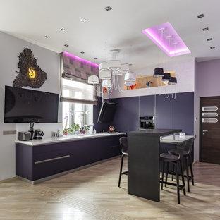 На фото: п-образная кухня-гостиная в современном стиле с плоскими фасадами, фиолетовыми фасадами, островом, монолитной раковиной, белым фартуком, черной техникой, бежевым полом и белой столешницей с