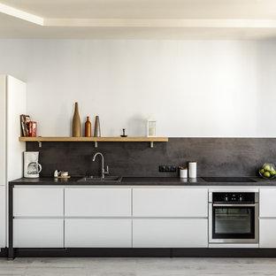 Пример оригинального дизайна интерьера: линейная кухня в современном стиле с накладной раковиной, плоскими фасадами, белыми фасадами, черным фартуком, техникой из нержавеющей стали, серым полом и черной столешницей без острова