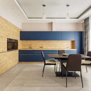 Пример оригинального дизайна: угловая кухня в современном стиле с обеденным столом, плоскими фасадами, синими фасадами, бежевым фартуком, фартуком из дерева, бежевым полом, бежевой столешницей и техникой из нержавеющей стали без острова