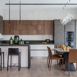 Пример оригинального дизайна: угловая кухня в современном стиле с накладной раковиной, плоскими фасадами, фасадами цвета дерева среднего тона, светлым паркетным полом, полуостровом, бежевым полом и серой столешницей