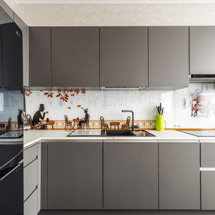 Идея дизайна: угловая кухня в современном стиле с плоскими фасадами, серыми фасадами, разноцветным фартуком, черной техникой, серым полом и белой столешницей