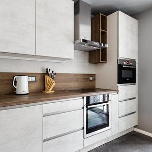 Выдающиеся фото от архитекторов и дизайнеров интерьера: кухня в современном стиле с плоскими фасадами, белыми фасадами, серым полом и коричневой столешницей