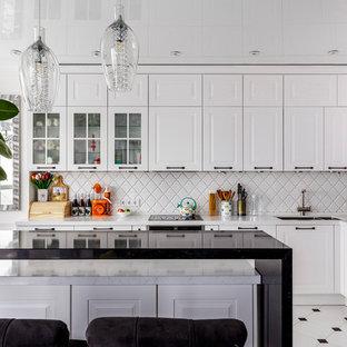 На фото: угловая кухня в скандинавском стиле с врезной раковиной, белыми фасадами, белым фартуком, черной техникой, островом, фасадами с выступающей филенкой и белым полом с