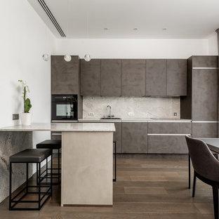 Пример оригинального дизайна: кухня в современном стиле с обеденным столом, плоскими фасадами, коричневыми фасадами, бежевым фартуком, фартуком из каменной плиты, черной техникой, паркетным полом среднего тона, полуостровом и бежевой столешницей